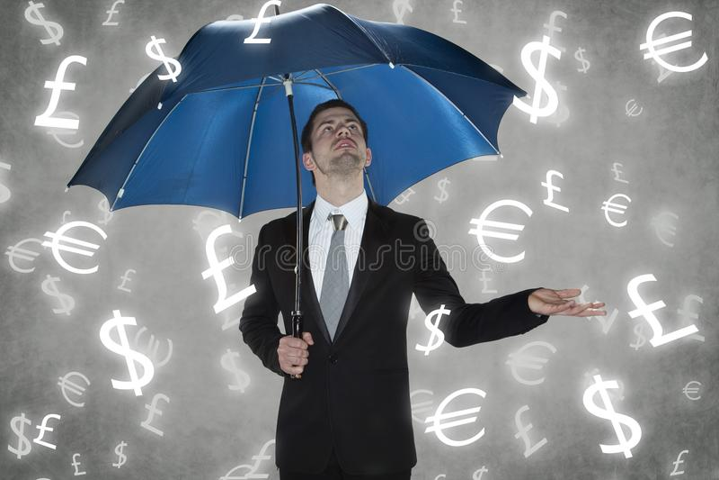 Affärsman under regnvalutorna arkivfoto