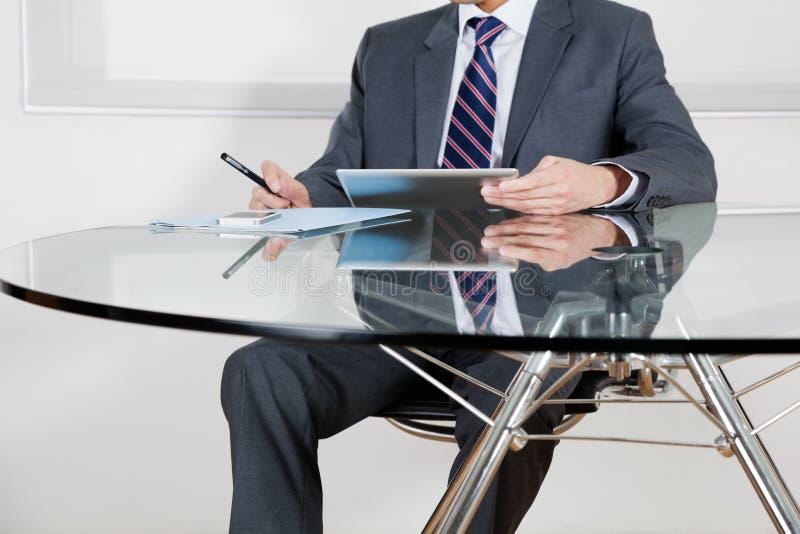Affärsman Using Digital Tablet i regeringsställning royaltyfri bild