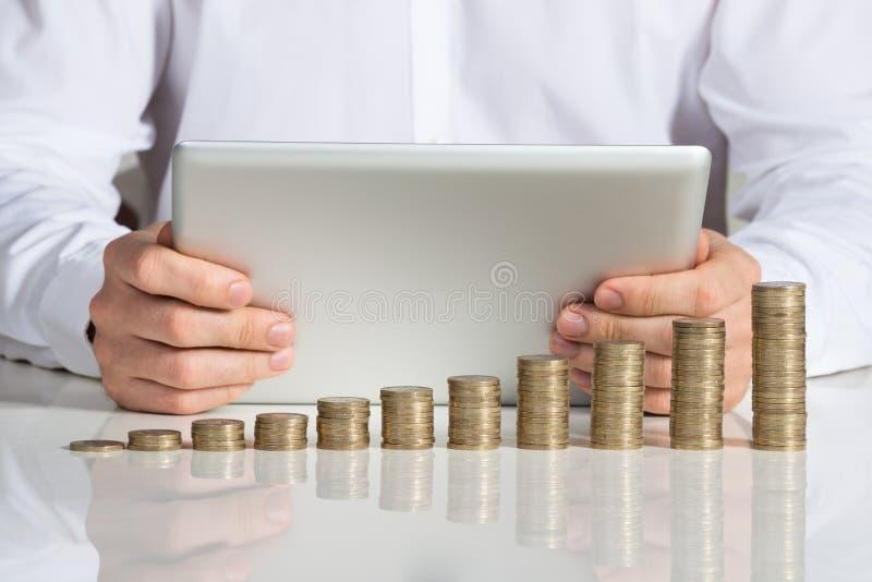 Affärsman Using Digital Tablet med staplade mynt på skrivbordet royaltyfri foto