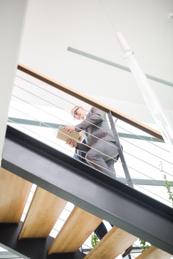 Affärsman Using Digital Tablet, medan flytta sig uppför trappan i regeringsställning royaltyfri bild