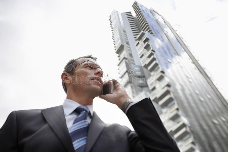 Affärsman Using Mobile Phone mot högväxt byggnad arkivfoto
