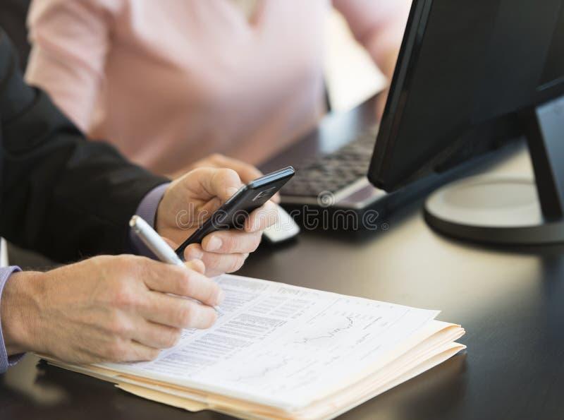 Affärsman Using Smart Phone, medan skriva på dokument på skrivbordet fotografering för bildbyråer