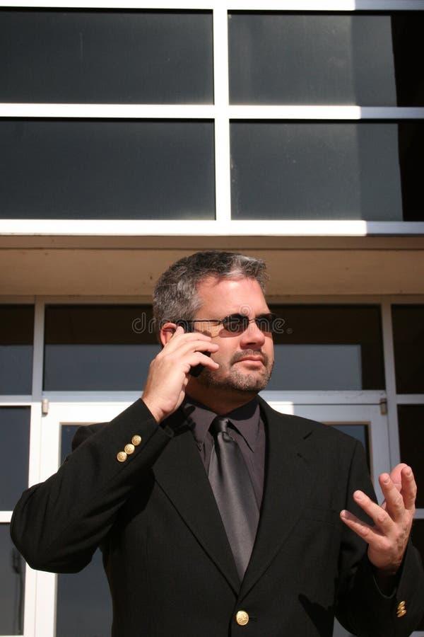 affärsman utanför telefonen royaltyfria bilder