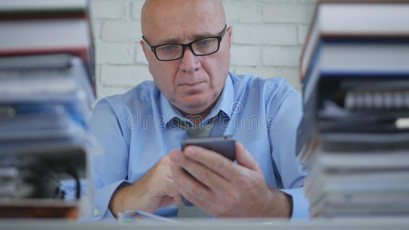Affärsman Wearing Eyeglasses Text som i regeringsställning använder mobiltelefonen royaltyfri bild