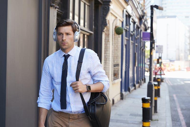 Affärsman Wearing Wireless Headphones som går för att arbeta arkivbilder
