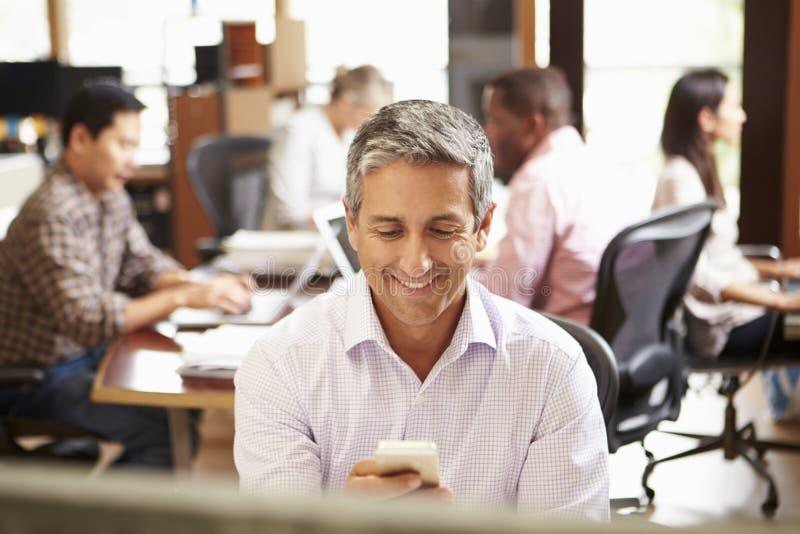 Affärsman Working At Desk som använder mobiltelefonen arkivfoto