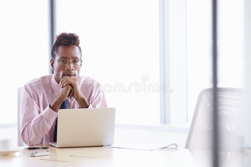 Affärsman Working On Laptop på styrelsetabellen royaltyfria foton