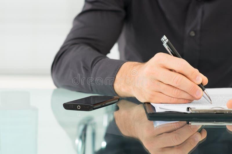 Affärsman Writing en skrivbordsarbete royaltyfria foton