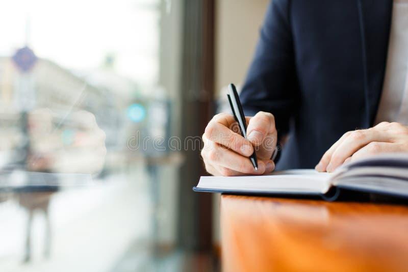 Affärsman Writing i stadsplanerare på kaféfönstret arkivfoto