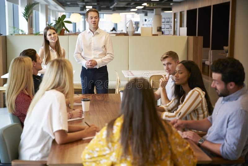 AffärsmanAnd Businesswoman Addressing grupp av unga kandidater som sitter runt om tabellen arkivfoto
