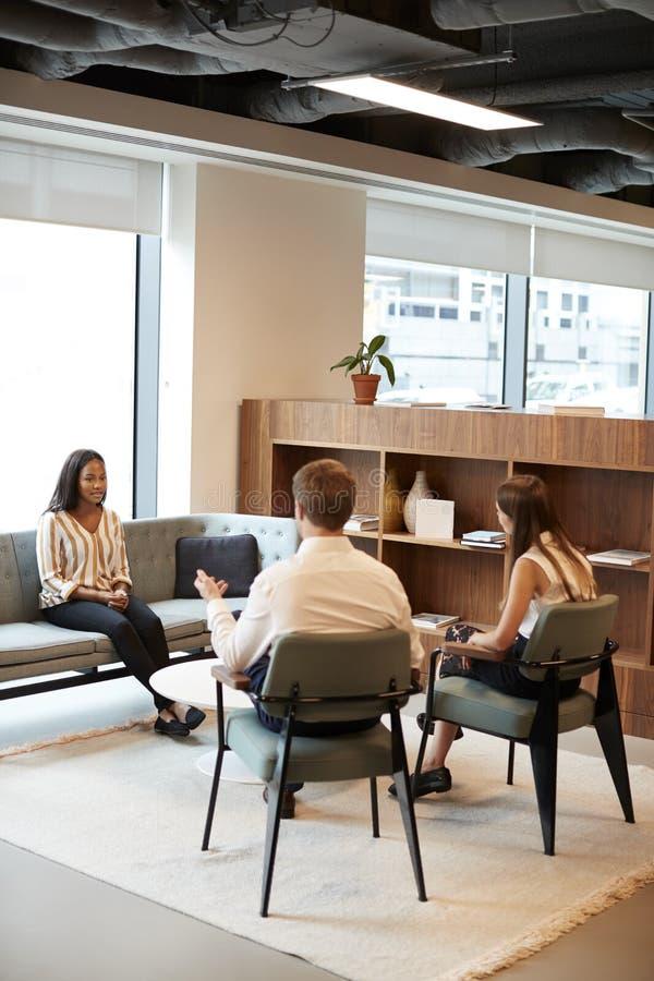 AffärsmanAnd Businesswoman Interviewing kvinnlig kandidat i regeringsställning på den doktorand- rekryteringbedömningdagen royaltyfria bilder