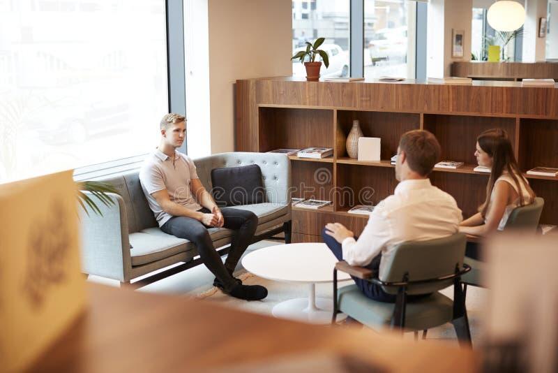 AffärsmanAnd Businesswoman Interviewing manlig kandidat i regeringsställning på den doktorand- rekryteringbedömningdagen arkivfoton