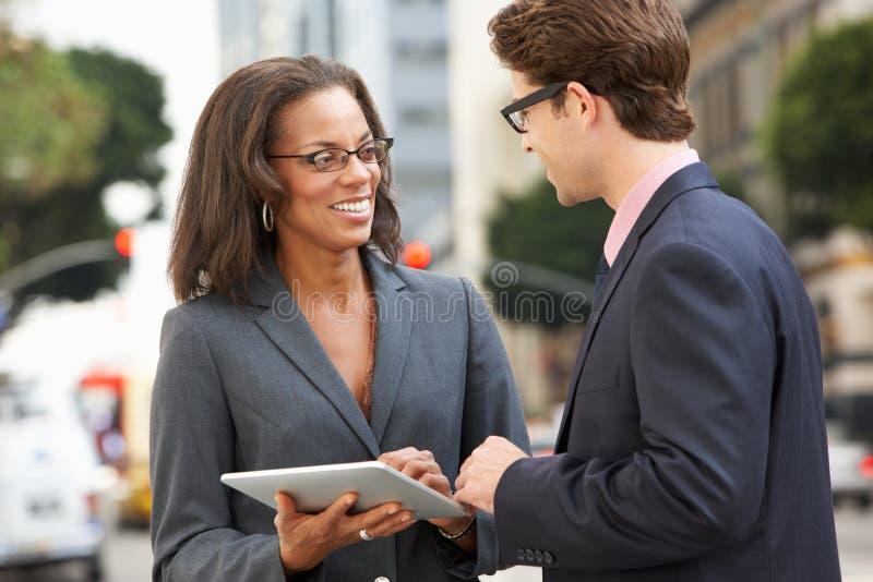 AffärsmanAnd Businesswoman Using Digital minnestavla utanför royaltyfri bild