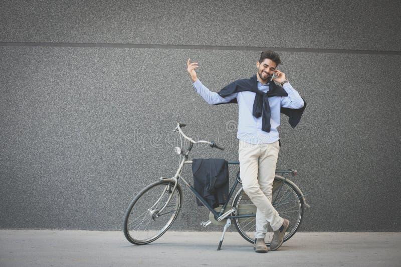 Affärsmananseende bredvid en cykel och samtal på telefonen royaltyfri foto