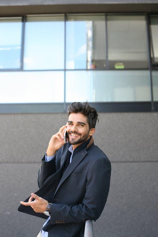 Affärsmananseende bredvid väggen och samtal på den smarta telefonen Lo arkivbild