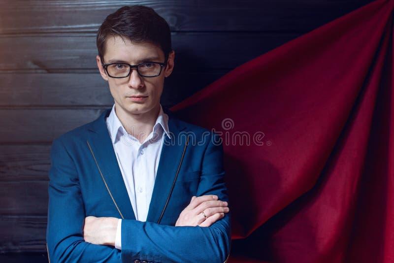 Affärsmananseende i en dräkt och röd kappa som superhero arkivfoto