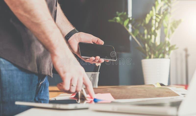 Affärsmananseende i ett kontor nära tabellen och att bläddra igenom en katalog och ett innehav en smartphone arkivfoton