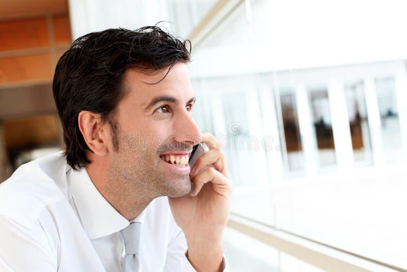 Affärsmananseende i hallet som talar på telefonen arkivbild