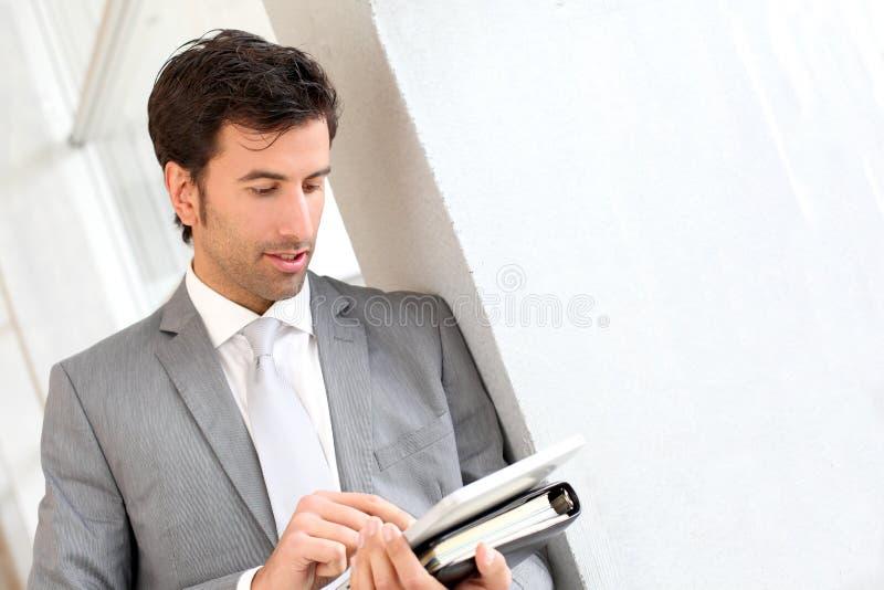 Affärsmananseende i korridor genom att använda minnestavlan arkivfoton