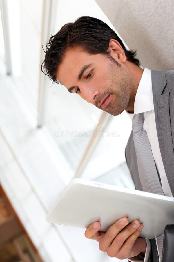 Affärsmananseende i korridor genom att använda minnestavlan royaltyfria foton