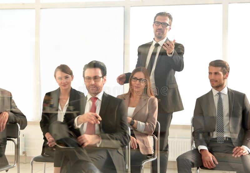 Affärsmananseende som tilltalar kollegor på mötet arkivfoton