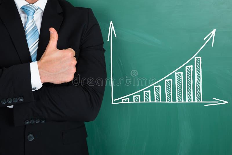 Affärsmananseende vid grafen som dras på den svart tavlan royaltyfri bild