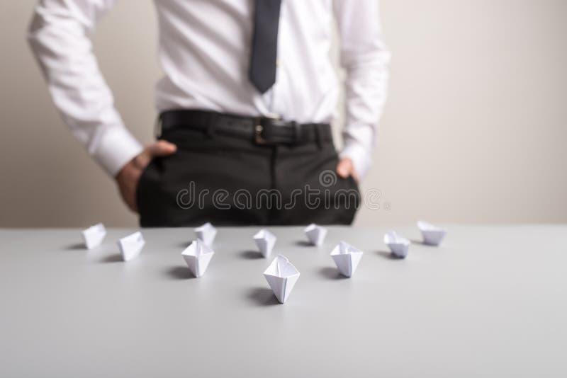 Affärsmananseendet bak ett skrivbord med origamipapper gjorde fartyg royaltyfri fotografi