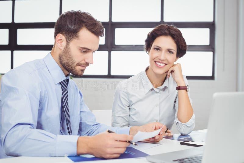 Affärsmanarbete medan lyckligt kvinnligt kollegasammanträde beside royaltyfri foto