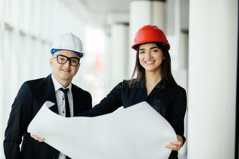 Affärsmanarkitekter ser den pappers- arkitekten för planaffärskvinnan i regeringsställning för att diskutera affärsprojekt i rege royaltyfri bild