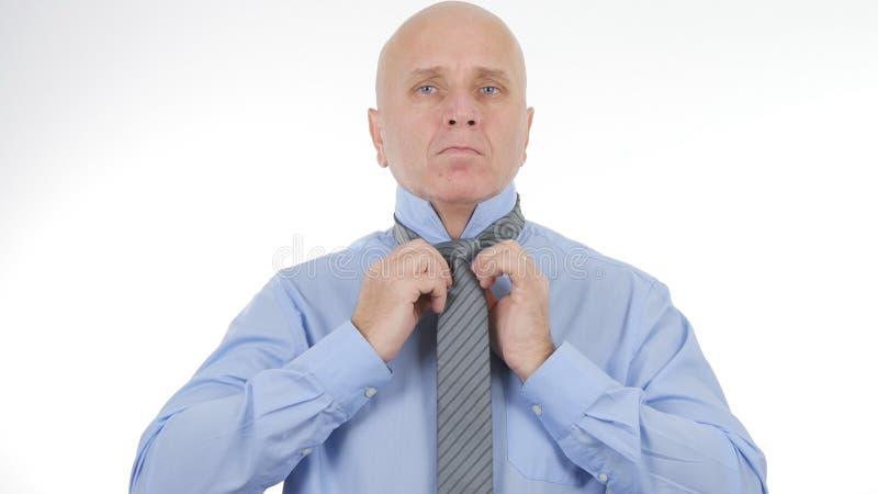 AffärsmanArranging His Knot band för ett affärsmöte arkivbild