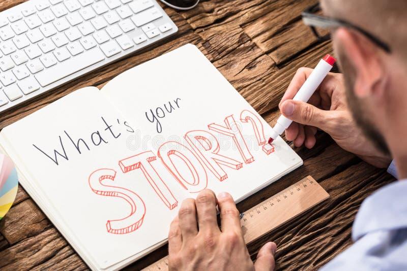 AffärsmanAsking What ` s din berättelse på anteckningsboken arkivfoto