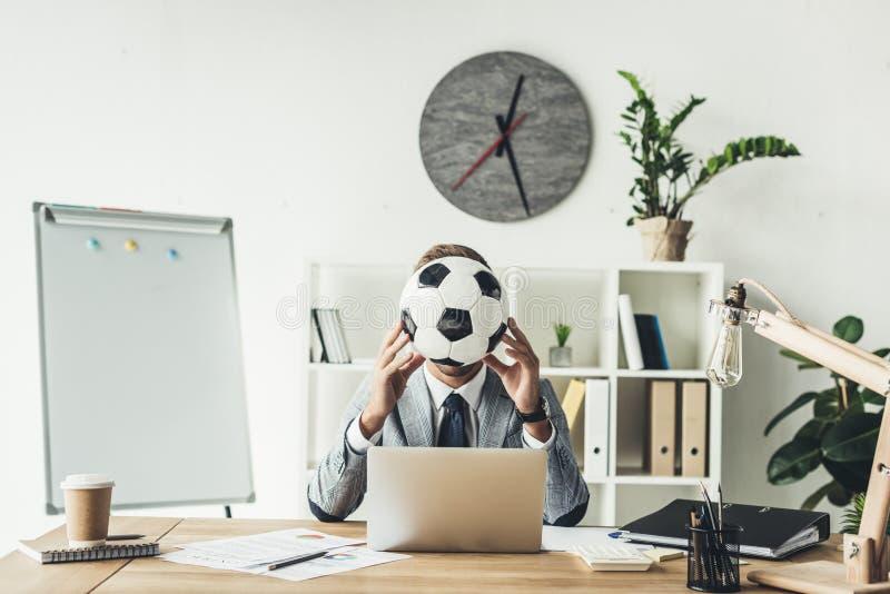 affärsmanbeläggningframsida med fotbollbollen royaltyfria foton