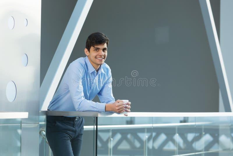 Affärsmanbenägenhet på balkongräcke arkivbild