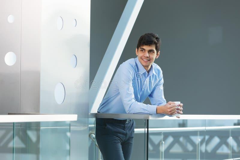 Affärsmanbenägenhet på balkongräcke royaltyfri foto