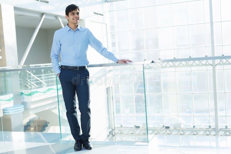 Affärsmanbenägenhet på balkongräcke royaltyfria foton
