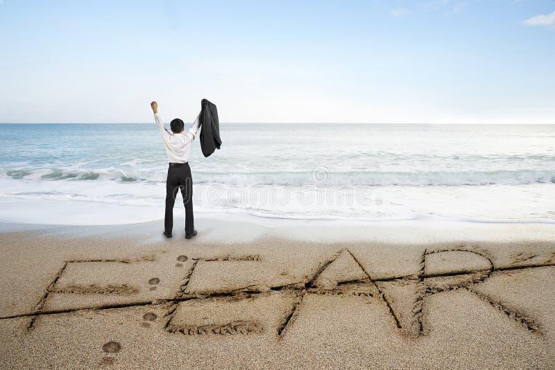 Affärsmanbifallet med skräckord tog bort linjen på sandstranden royaltyfri fotografi