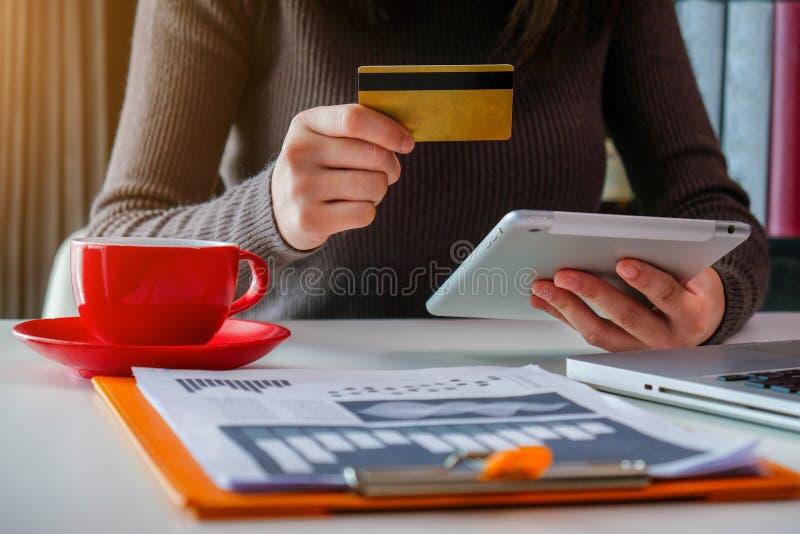 Affärsmanbrukskreditkorten till att shoppa direktanslutet i internetwebsite shoppar med datorbärbara datorn arkivfoton