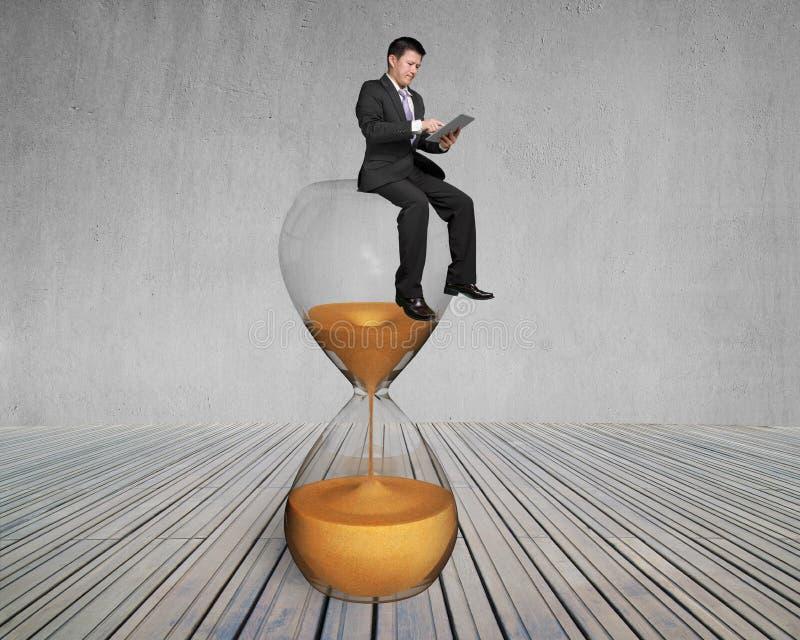 Affärsmanbruksminnestavlan och sitter på timmeexponeringsglas royaltyfria bilder