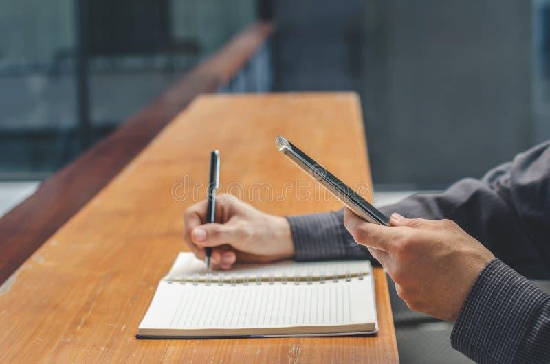 Affärsmanbrukssmartphone, medan göra anmärkningar i anteckningsbok Student som direktanslutet lär Man som använder grejen royaltyfria bilder