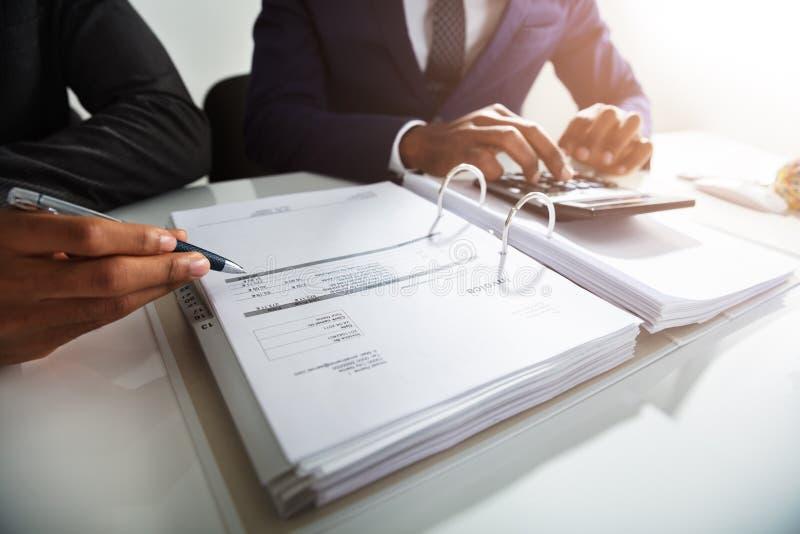 AffärsmanCalculating Bills Using räknemaskin royaltyfria bilder