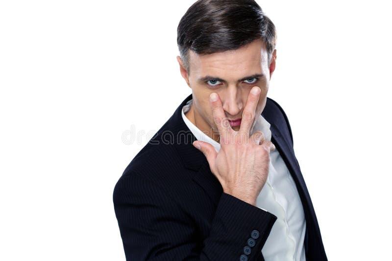 Affärsmandanande som håller ögonen på dig att göra en gest royaltyfri foto