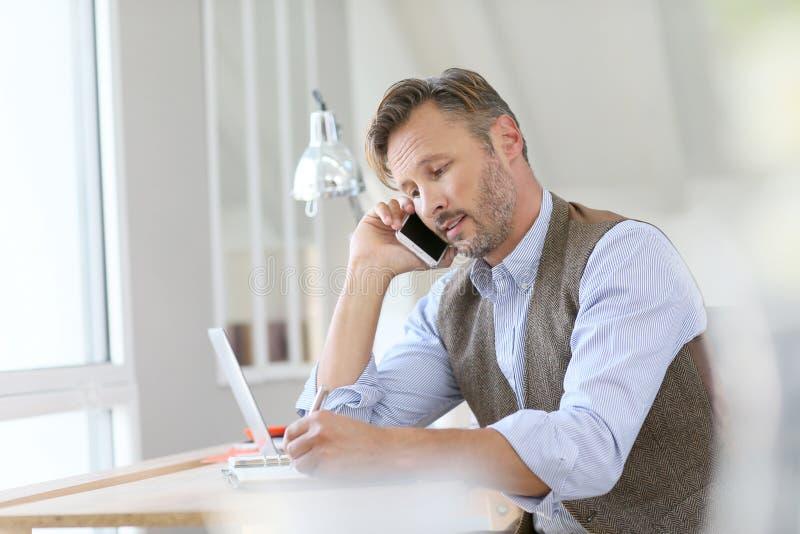 Affärsmandanandeaffär på telefonen royaltyfri bild