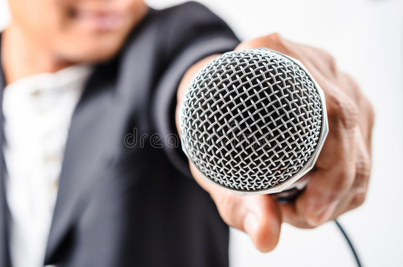 Affärsmandanandeanförande med att göra en gest för mikrofon och för hand fotografering för bildbyråer