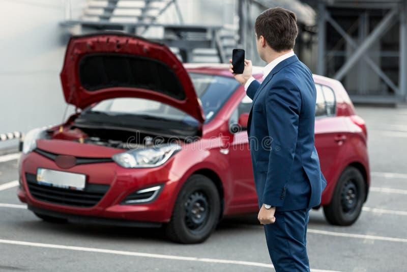 Affärsmandanandefoto på telefonen av sammanbrottbilen för försäkring arkivfoton