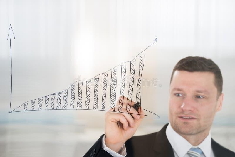 AffärsmanDrawing Graph On glasvägg i regeringsställning arkivfoto