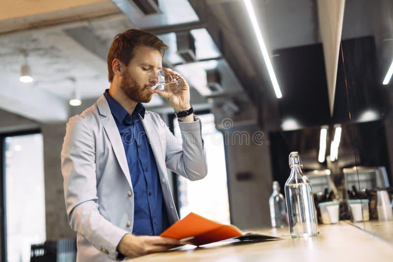 Affärsmandricksvatten och läsningpapper arkivbilder