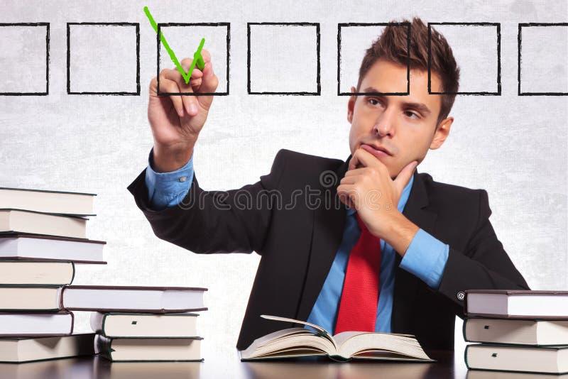 Affärsmanen som kontrollerar en lista av, bokar honom läste arkivfoton