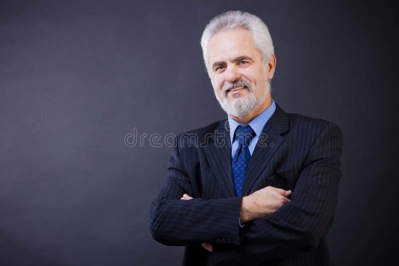 Affärsmanen som ler med, beväpnar korsat arkivbilder