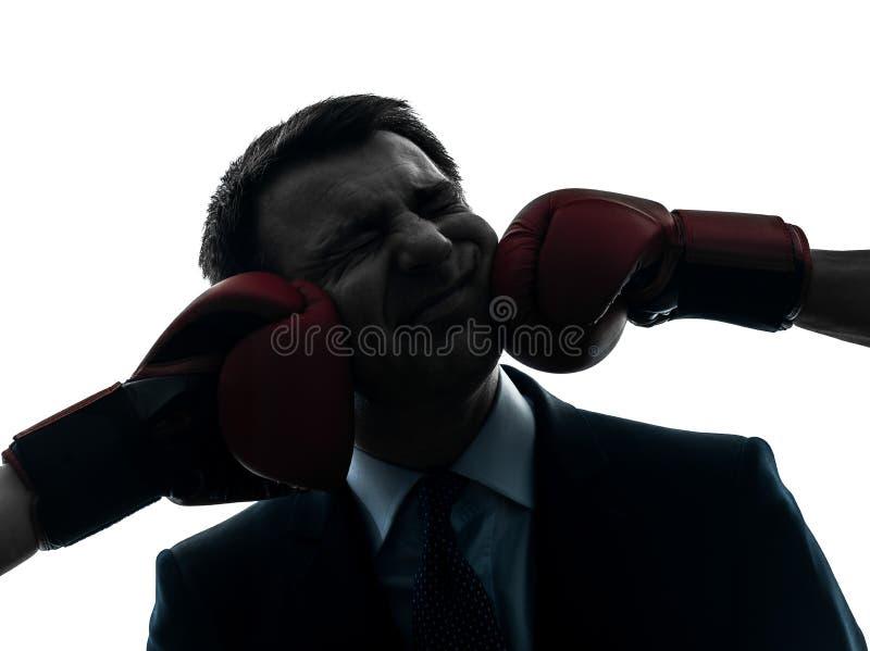 Affärsmanen stansar, genom att boxas handskesilhouetten arkivfoto