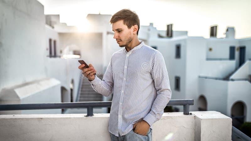 Affärsmanfreelancerbloggeren med smartphonen i händer, man i randig skjorta står den utomhus- gatan på terrass i Grekland Honom arkivfoton